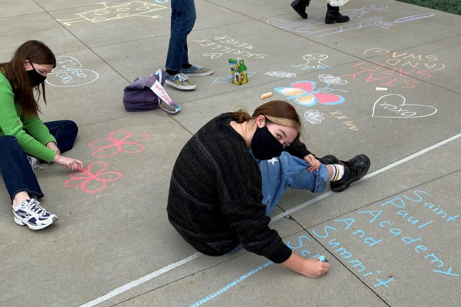 Seniors Isobel Alm and Hannah Lorenz-Meyer color the pavement with flowers and SPA logos.