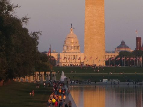 The sun sets on the U.S. Capitol and Washington Monument, which reflect in the Lincoln Memorial Reflecting Pool in Washington, D.C. Photo by Nikolas Liepins.