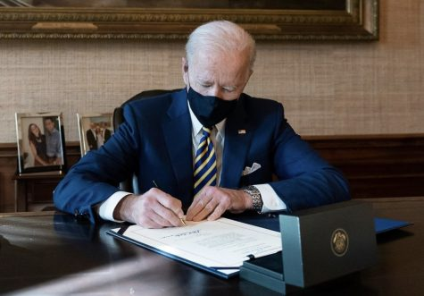 President Biden signing executive orders within the first days of his term in office.