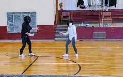 Fencing coach Sasha guides a student by holding the Foil weapon to demonstrate a movement.