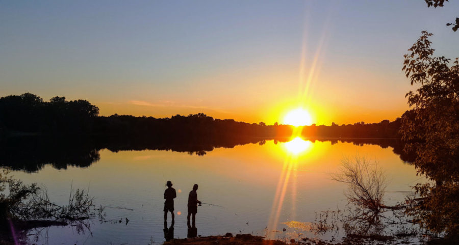 Two men fish on the clear glasslike lake with the sun setting in the distance.