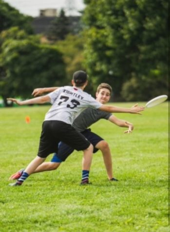 This is a photo of Levi Smetana playing ultimate in 9th grade. Here, he throws the disc around the defender.