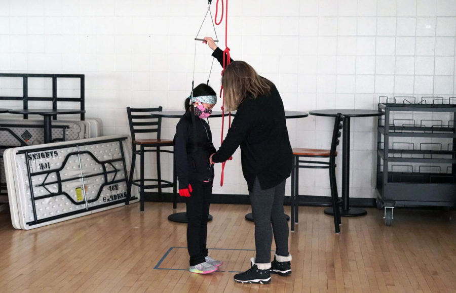 Coach Debbie Warne-Jacobsen readies a harness for Lydia Chen, in order to lift the skater up into the air to practice spinning.