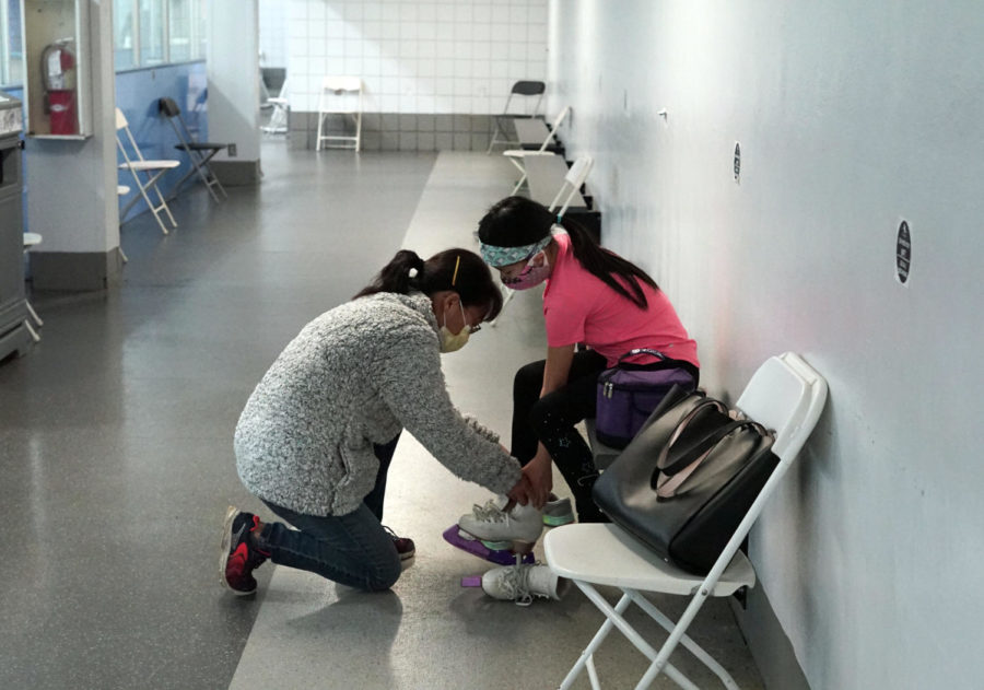 Chen's mother Helen Wang ties her skates before she goes into the ice.