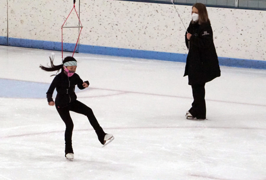 Warne-Jacobsen uses the same method she used to train Chen earlier, using the harness to let Chen practice spinning in the air on ice.