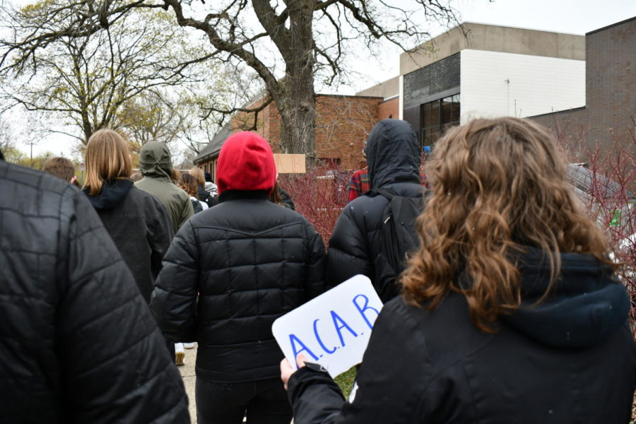 Senior Elaina Parsons holds an ACAB sign has students march around campus to the main green area.