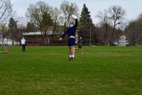 During practice, senior Jackson Biggs jumps to catch the frisbee midair.