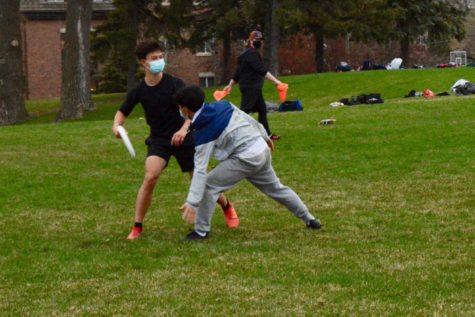 Sophomore Ben Chen tries to get frisbee around junior Pah Na during practice.