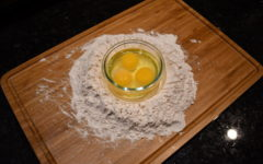 This image shows one of the first stages of making pasta. Eventually, these eggs and flower will create tasty pasta!