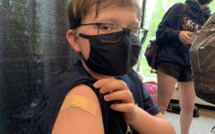 7th-grader Howard Huelster shows off his vaccination bandage.