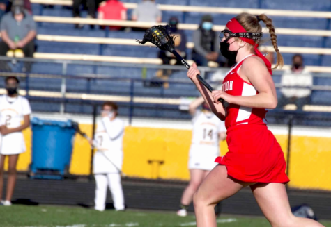 """Senior Erin Magnuson cradles the ball during an away game. """"I got into both [sports] because my parents played. My mom played lacrosse and suggested [that I] try it, and my dad played hockey, so both my sister and I tried it [too]. I love the intensity of sports and the feeling of accomplishment when I do something well or reach a goal I have set for myself, which is why I really enjoy playing,"""" Magnuson said."""