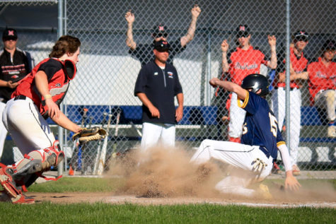 Ninth-grader John Christakos slides onto home base as dust flies around him. Christakos has stepped up for the team, even as a new player, having played in nine games so far this season.
