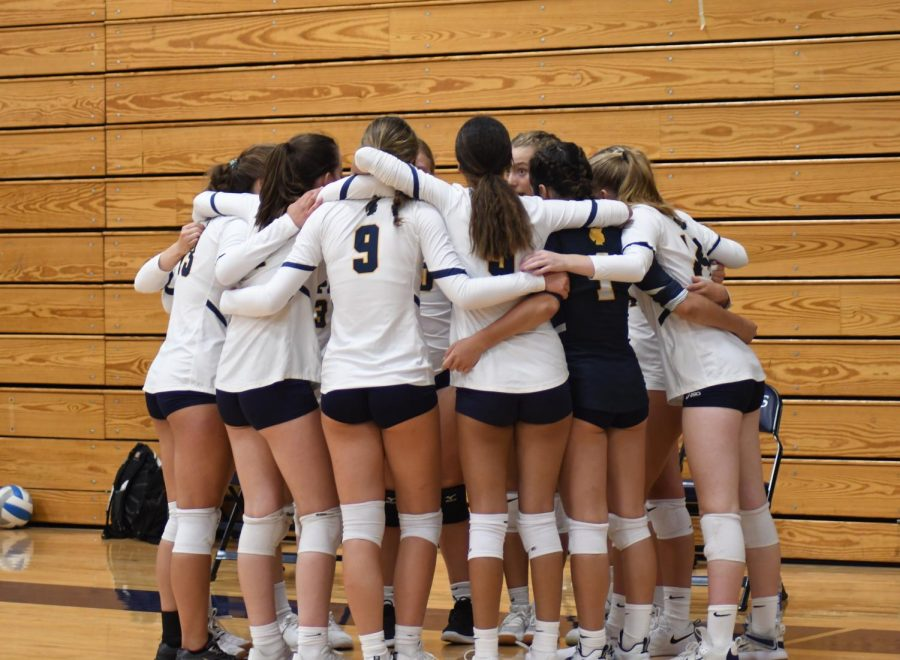 The Spartan volleyball team prepares for the home opener against South St. Paul Aug. 31 by getting into a group huddle.