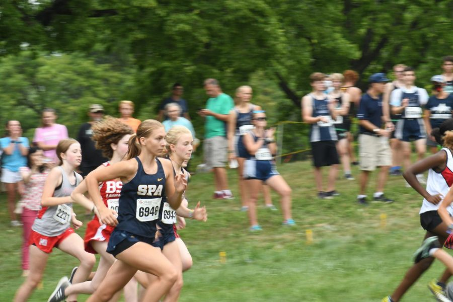 """PACE YOURSELF. Freshmen Inga Wing and Helen Townley sprint to the finish line in a 2-mile race. Sophomore Ford Reedy said, """"My favorite part of being on the team is everybody on it."""""""
