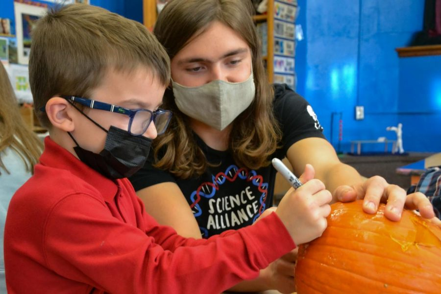 Senior Will Sedo helps a kindergartener draw a face on his pumpkin before they begin carving the pumpkin out. Sedo noted he really enjoyed, helping [the lower school student]s bring their pumpkin carving ideas to life.