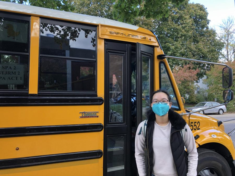 """THANKS FOR THE RIDE. Freshman Deling Chen stands in front of a school bus as she waits for the doors to open. Although there has been a bus driver shortage devastating school schedules throughout the nation, Saint Paul Academy hasn't had to cancel any bus routes. """"[Having to cancel bus routes] hasn't been too difficult for SPA,"""" Director of Transportation Melissa Douden said, """"For other schools it's been a very big challenge."""""""