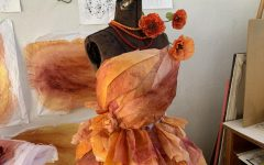 Besse is using handmade sheets of colorful tissue paper taped and folded together to build the dress.